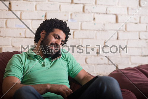 casual middle eastern young businessman talking on the phone, and tablet used in modern stylish office