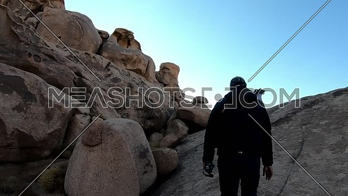 Follow shot for male tourist climbing Sinai/moses  Mountain at sunset.