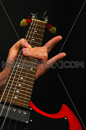 Male hand holding red sg guitar neck with devil horns rock metal sign isolated on black background