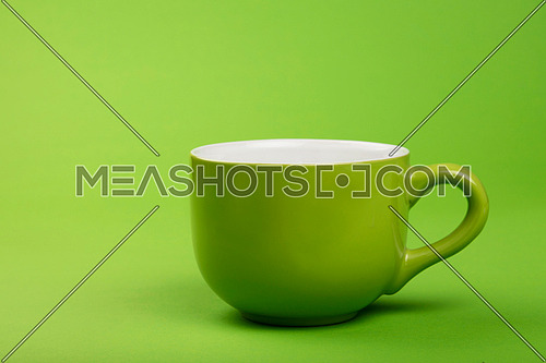 One full big coffee or tea green cup on green paper background, side view, low angle