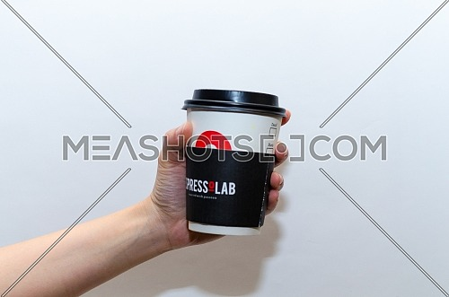 female holding a paper cup of EspressoLab ( espresso lab ) with it's black paper cup; December 2018 in Cairo - Egypt