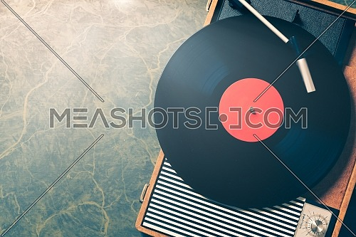 Older Gramophone with a vinyl record on wooden table, top view and copy space,vintage style with split toning.