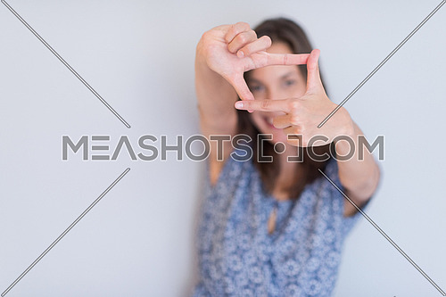 young happy woman showing framing hand gesture isolated on a white background