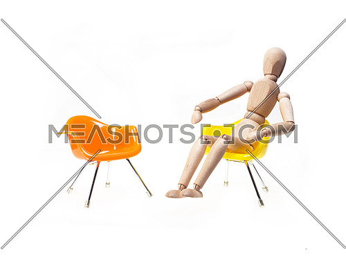 wood mannekin waiting for meeting sitting on chair over white