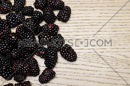 Fresh blackberries filling half of the frame on a wooden light background