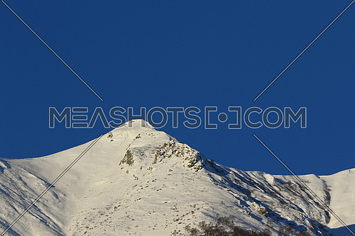 Mountain peaks and valley covered in snow with clear blue skies