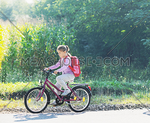 schoolgirl traveling to school on bicycle at early morning on beautiful nature