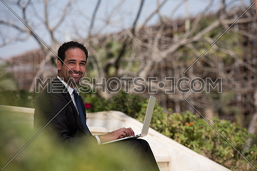 Handsome business executive sitting on stairs if a corporate building working on laptop