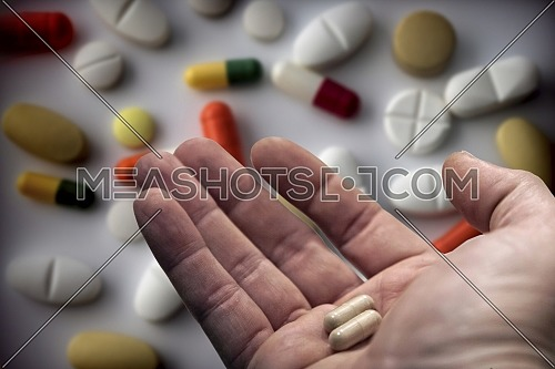 middle-aged man's hand holding two pills, Taking daily medication