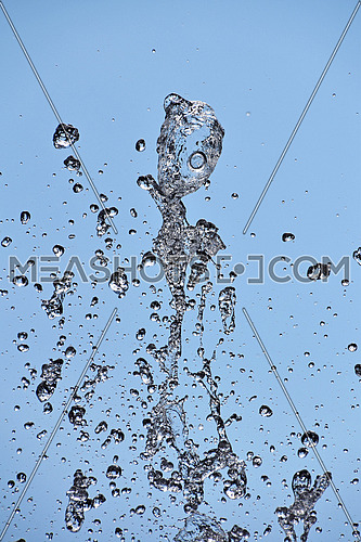 Close up water drops of fountain stream splash over background of clear blue sky