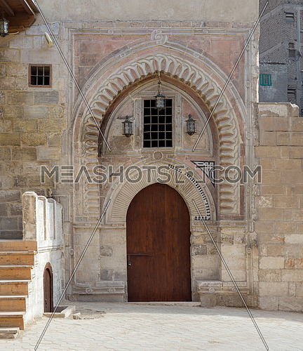 Gate of Darb Al Labana alley, a Bahari Mameluke era gate with small window covered with iron bars and decorated with wooden and stone decorative elements with geometric designs