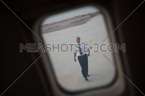 Young middle eastern successful pilot walking towards private jet