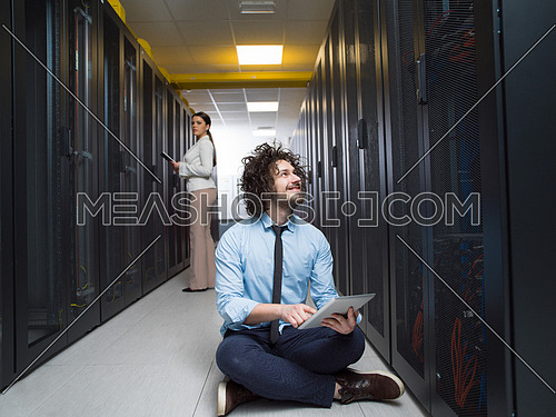 Team of young technicians working together on servers at the data center using tablet computers