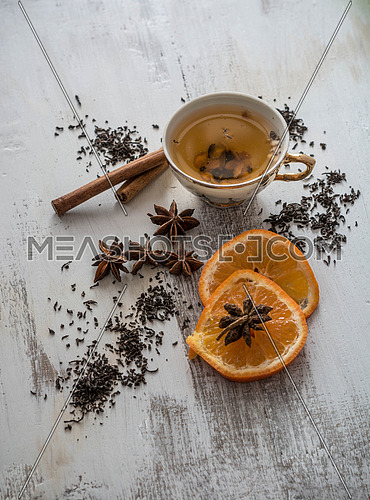 Tea, dried cinnamon,orange and anise on wooden background