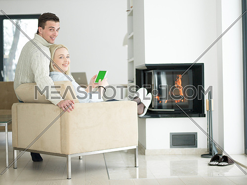Young Couple in front of fireplace surfing internet using digital tablet on cold winter day at home
