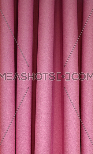 Heavy purple pink pleated felt textile curtain background with portiere drape folds, side view close up