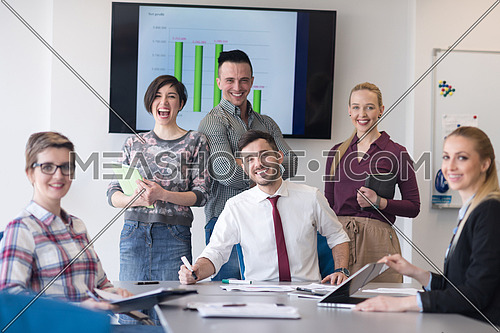 portrait of business people group at modern bright startup office meeting room, young  man with beard sitting  in middle as team leader