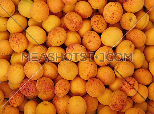 Fresh ripe mellow apricots background pattern close up, top view