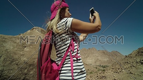 Follow shot for a female tourist wearing a pink cap and travel backpack taking photos using mobile phone at Sinai Mountain for wadi Freij at day.