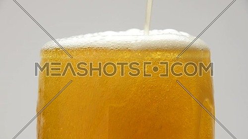 Close up background of pouring beer, sparkling wine or champagne with bubbles in glass, low angle side view, slow motion