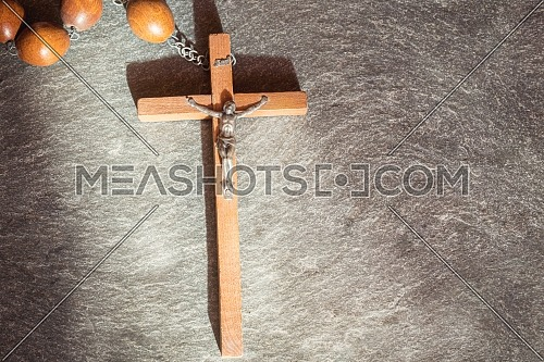 Old wooden Franciscan rosary, on the large Christian cross Jesus, a ray of sunshine illuminates the rosary on a gray stone background, religious and faith concept.