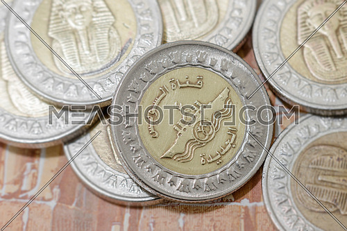 many pieces Egyptian 1 pound rare gold and silver metal coins with new Suez canal print  dropping on Egyptian pound paper note - banknote  background