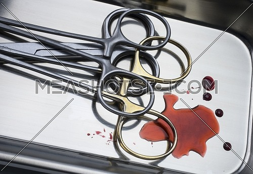 Several suture scissors on a silver tray, traces of blood, conceptual image, horizontal composition