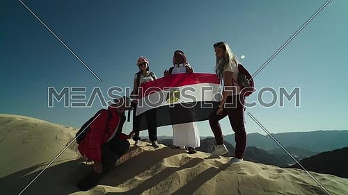 Follow shot for group of tourists and bedouin guide holding Egyptian flag while exploring Sinai Trail from Ain Hodouda at day.