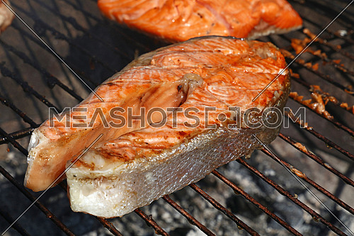 One grilled salmon fish steak barbecue meal cooking, prepared on bbq grill, close up