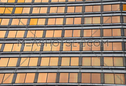 Orange colored glass windows of modern business office building at sunset in evening, low angle view perspective
