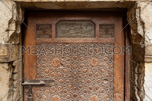 Geometrical engraved decorations of an aged wooden ornate door of Abd El Latif El Korafi historic mosque, signed by the maker, Gamalia district, Old Cairo, Egypt