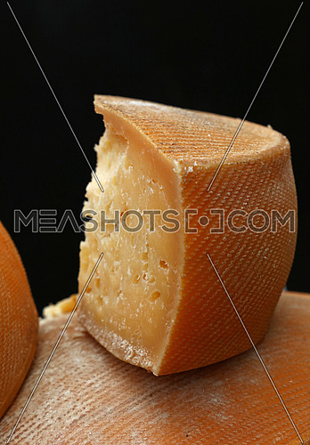 Cut slice block section of old aged matured hard artisan cheese over black background, close up, low angle view