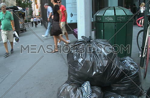 Long shot for shot for Trash on Street corner at New York City Showing people walking at day