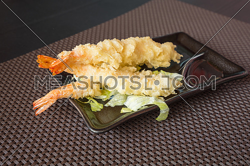 Japanese Cuisine,Tempura Shrimps (Deep Fried Shrimps) with sauce and vegetables on a black plate. Brown  background,shallow depth of field