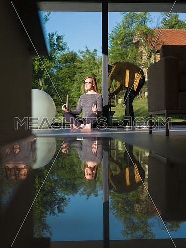A young handsome woman doing yoga exercises on the floor of her luxury home villa