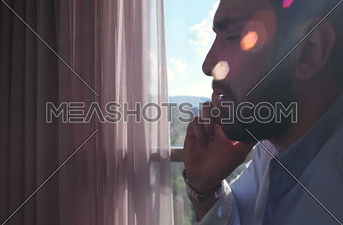 Business Man Talking On Cell Phone At Home with sun flares coming from window