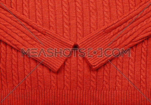 Close up background texture of red cable knitted wool jersey fabric sweater with row braid pattern