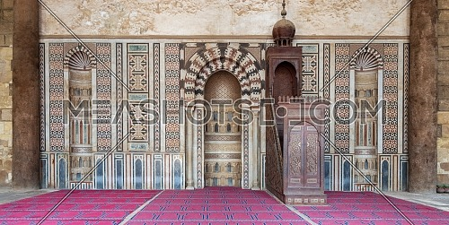 Colorful decorated marble wall with engraved Mihrab (niche) and wooden Minbar (Platform) at the public historical Mosque of Al Nasir Mohammad Ibn Qalawun, situated in the Citadel of Cairo in Egypt