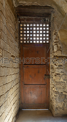 Facade of old abandoned stone bricks wall with one weathered wooden door and wooden grid window, Old Cairo, Egypt