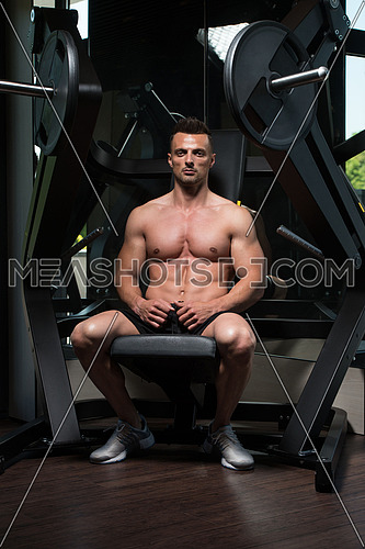 Healthy Young Man Resting In Healthy Club Gym After Exercising