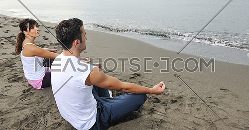 young couple people meditating yoga in lotus position at early morning on the beach