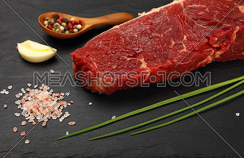 One raw beefsteak red meat cut, spices, peppercorn in wooden scoop, green spring chive, garlic and Himalayan salt on black slate board, close up, high angle view