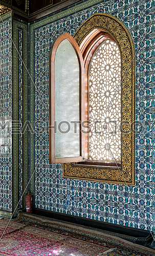 Wooden arched window framed by golden floral pattern ornaments over ceramic tiles wall with floral blue patterns at the public mosque of The Manial Palace of Prince Mohammed Ali Tewfik, Cairo, Egypt