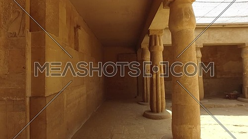 Reveal shot for small pharaonic temple in Saqqara Area showing paintings on wall and columns at day.