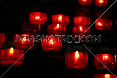Red translucent candles burning in dark church, close up, low angle view