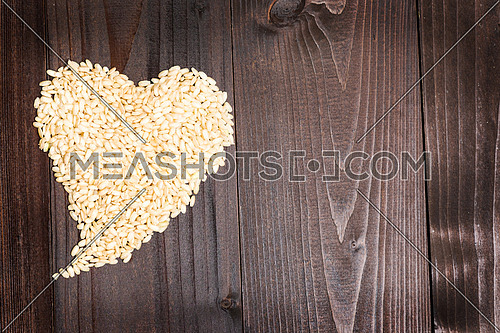 In the picture an heart formed by grains of rice on background of wood with empty space.
