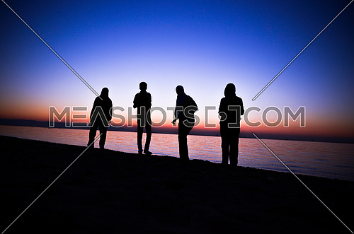 Four friends standing and having fun at the beach enjoying the golden hour by sunset