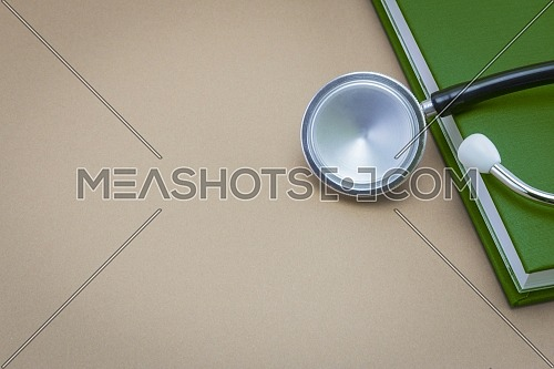 stethoscope and a book on brown background