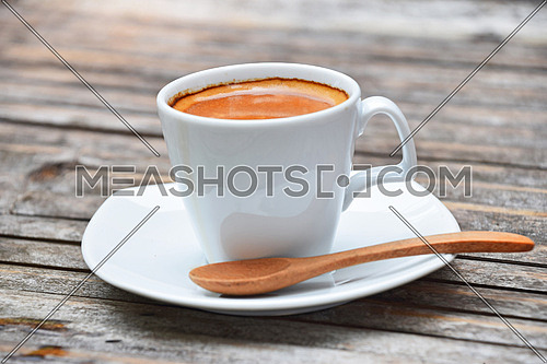 One white cup full of espresso coffee with brown crema on porcelain saucer with wooden spoon on old vintage bamboo table
