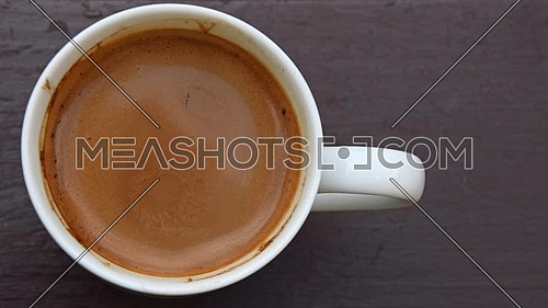 Close up one white cup full of coffee with milk on wooden table with slow motion animated cinemagraph spin of coffee froth, elevated top view, directl